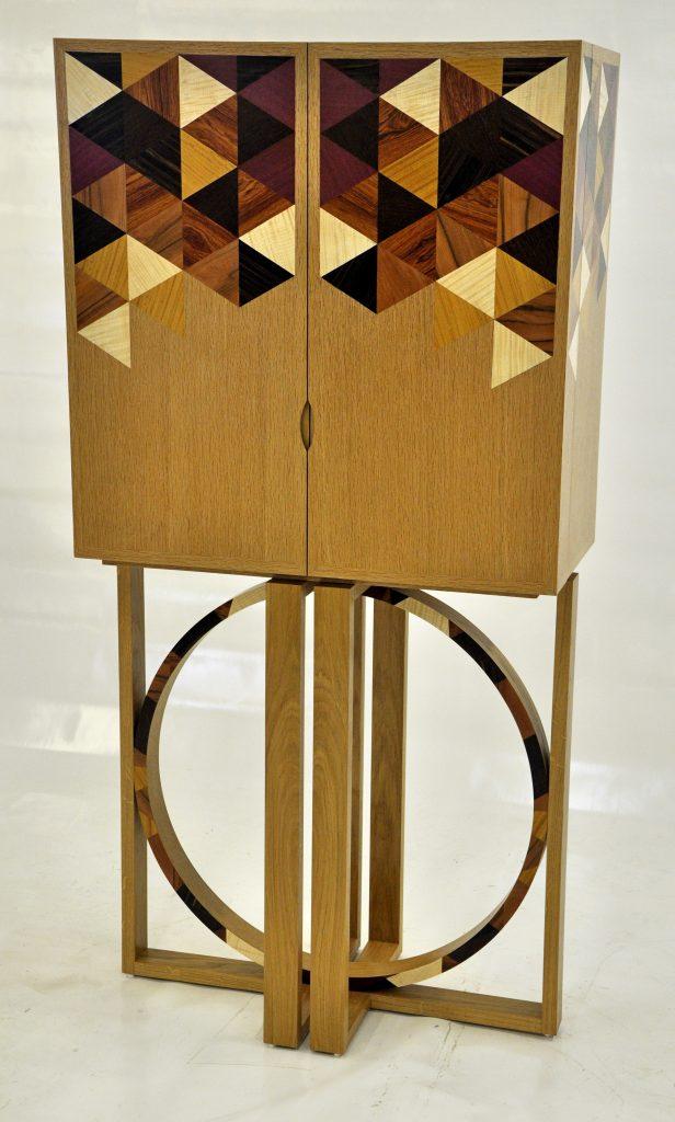 Cabinet contemporain deux portes, décoré de frisages en jeu de fond, diverses essences, piétement chêne massif avec pièces cintrées.