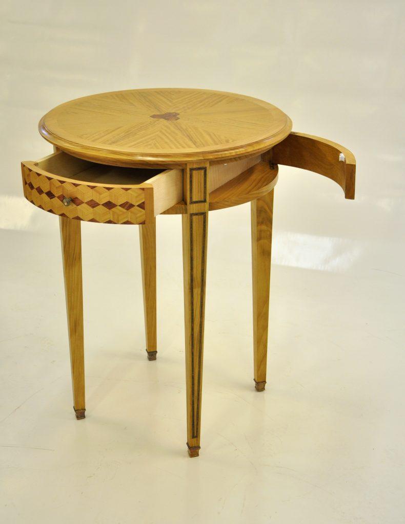 Petite table ronde d'inspiration Louis XVI avec tiroir et porte cintrés, filets incrustés, frisage en cubes sans fond et en soleil.
