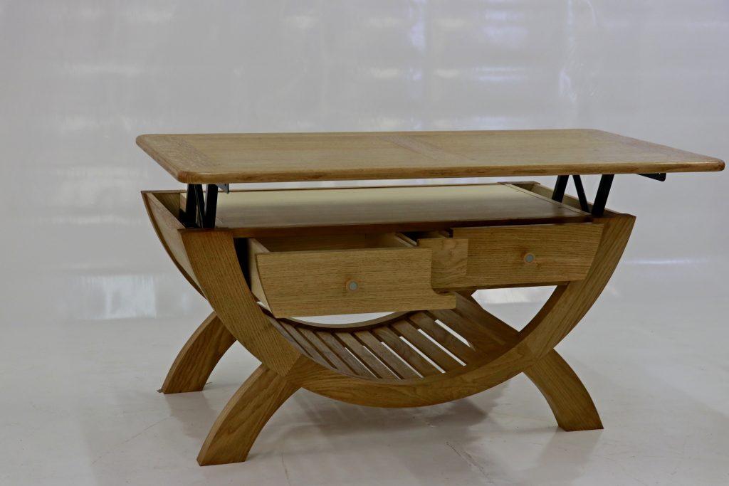 Table basse contemporaine en chêne massif, structure cintrée, plateau relevable.