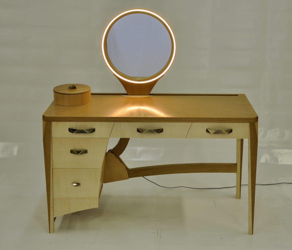 Coiffeuse contemporaine avec miroir rond escamotable plaquée de sycomore ondé, chêne avec frisage en soleil.