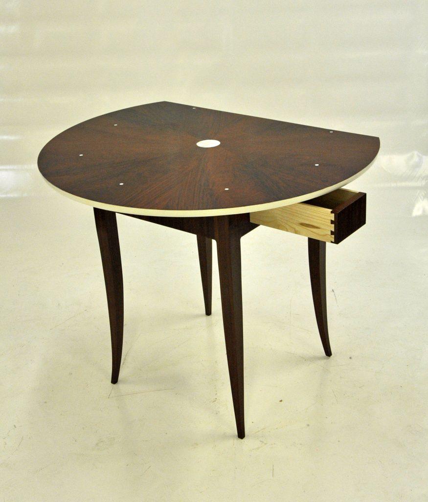 Console contemporaine transformable en table ronde sur quatre pieds sabres, plaquée d'acajou, motif de plateau en papillon.